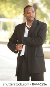 Image of a young African American businessman reaching in his pocket