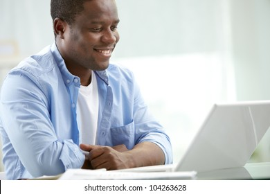 Image of young African businessman looking at laptop screen at workplace
