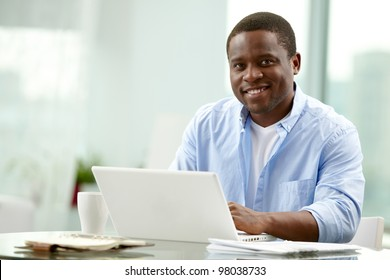 Image of young African businessman looking at camera at workplace