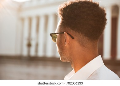 Image of young african man early morning looking aside outdoors.