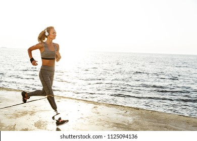 Image of young amazing disabled sports woman running on the beach outdoors listening music with headphones.