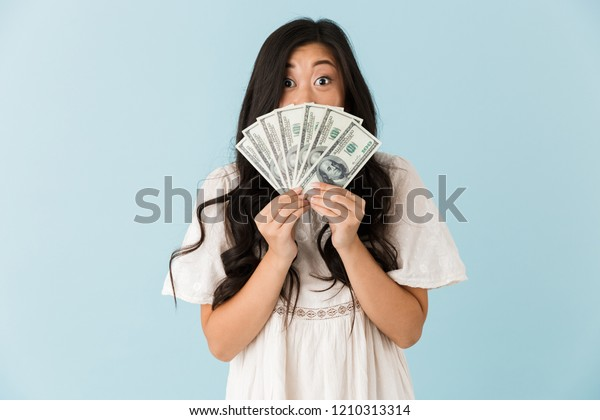 Image of young asian beautiful woman isolated over blue background holding money.