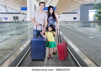 Image of young Asian family standing with suitcases on the airport escalator