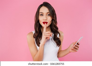 Image of young asian woman standing isolated over pink wall background looking camera using mobile phone showing silence gesture.