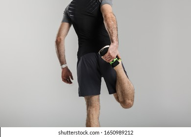 Image of young athletic man in sportswear stretching her leg while working out isolated over gray background