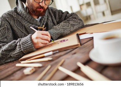 Image of young bearded man drawing