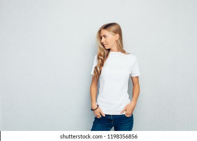 Image of a young beautiful girl dressed in a white t-shirt standing against a gray wall background posing.
