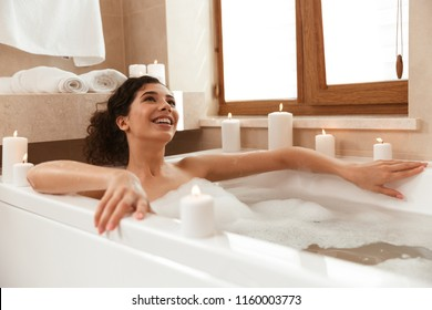 Image of young beautiful woman in bathroom lies resting in bath.