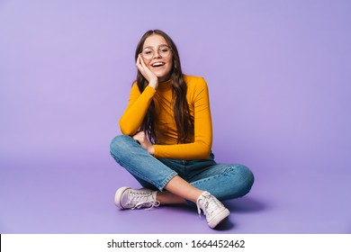 Image of young beautiful woman wearing eyeglasses smiling and sitting with legs crossed isolated over violet background