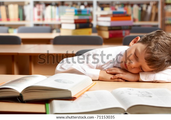 Image of young boy sleeping near books in the library