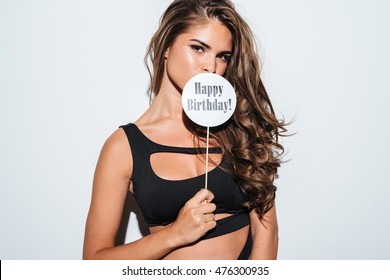 Image of a young brunette girl in bikini covering mouth with happy birthday sign on stick over white background