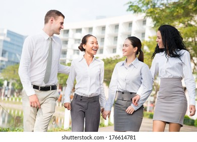 Image of a young business team talking while walking outside