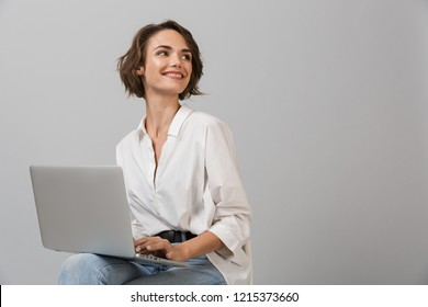Image of young business woman posing isolated over grey wall background sitting on stool using laptop computer.