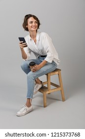 Image of young business woman posing isolated over grey wall background sitting on stool using laptop computer chatting by phone.