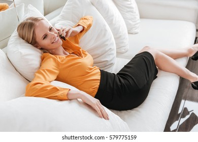 Image of young business woman sitting in office talking by phone. Looking aside.