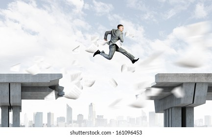 Image of young businessman jumping over gap in bridge