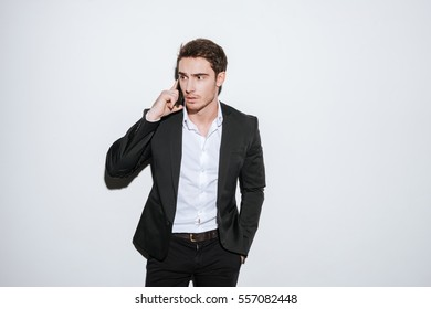 Image of young businessman posing at studio and look aside while talking by phone. Isolated over white background.