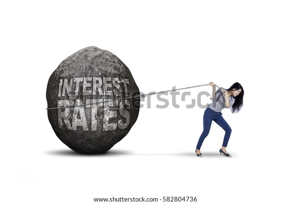 Image of young businesswoman dragging big stone with text of interest rates, isolated on white background