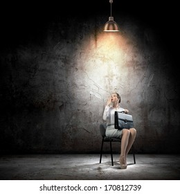 Image of young businesswoman sitting on chair under spot of light