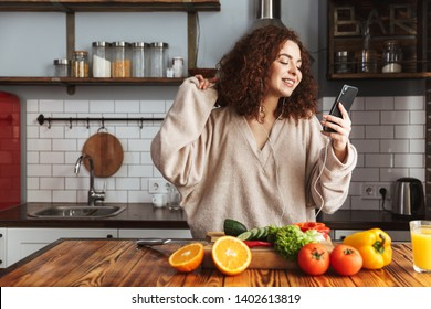 Image of young caucasian woman listening to music on mobile phone while cooking fresh vegetables salad in kitchen interior at home