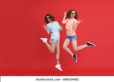 Image of young cheerful ladies friends jumping isolated over red background. Looking at camera.