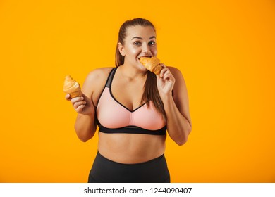 Image of young chubby woman in tracksuit eating croissants isolated over yellow background