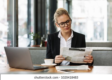 Image of young concentrated business woman sitting indoors in cafe using laptop computer reading newspaper.
