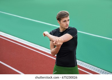 Image of young concentrated male athlete make stretching exercises outdoors. Looking aside.