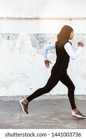 Image of a young concentrated muslim sports fitness woman dressed in hijab and dark clothes running outdoors.