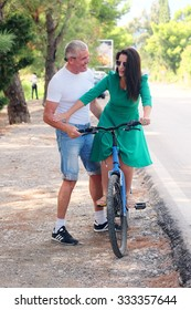 The image of young couple with bicycles in the city.