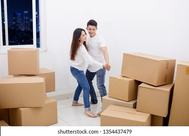 ff2c86940b Image of a young couple dancing after moving into their new apartment with  piles of cardboard