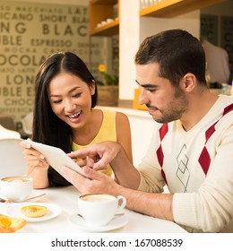 Image of a young couple networking with the digital tablet at a cafeteria