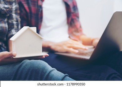 image of young couple or Two hipster find Real estate agent while holding house model and using laptop service online for Loan Mortgage Payment Property and customer. home loan and insurance concept