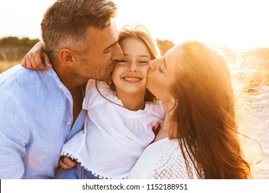 Image of young cute parents having fun together outdoors at the beach with their daughter.