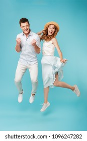Image of young excited caucasian people man and woman jumping isolated over blue background make winner gesture screaming.