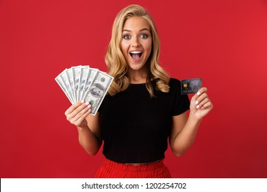 Image of young excited woman holding money and credit card isolated over red background.