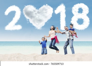 Image of young family having fun in the beach with clouds shaped heart and numbers 2018 in the sky