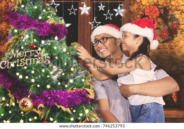 Image of young father helping his daughter to decorating a Christmas tree with an ornament ball