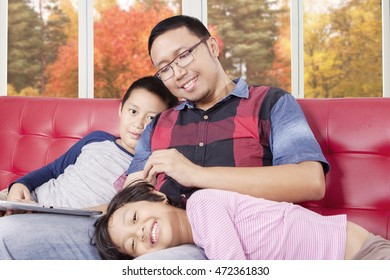 Image of young father and his children sitting on the sofa with a digital tablet, shot at home