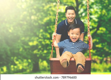 Image of young father pushing his son on the swing while having fun in the park