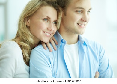 Image of young female embracing her husband and both looking forwards in new flat