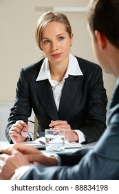 Image of young female looking at her partner while listening to him at meeting