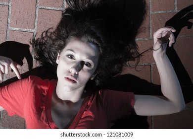 Image of a young female model wearing pretty red top lying on the floor of bricks.