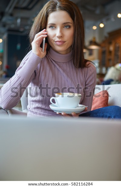 Image of young female reading sms on the phone in cafe