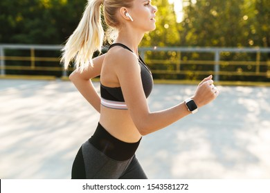 Image of young fitness woman wearing tracksuit and earpods running outdoors