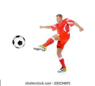 Image of a young football player with the ball in the red uniform. Isolated on white background