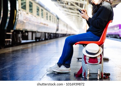 Image of Young freelance woman  working at train station before travel.