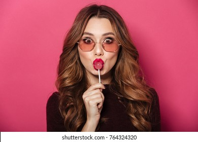 Image of young funny lady wearing glasses standing isolated over pink background. Looking camera eating candy.