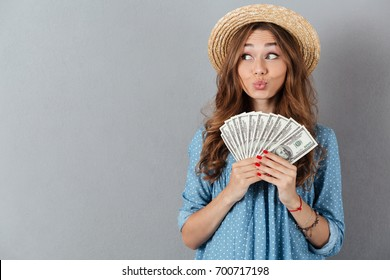 Image of young funny woman standing over grey wall wearing hat holding money. Looking aside.
