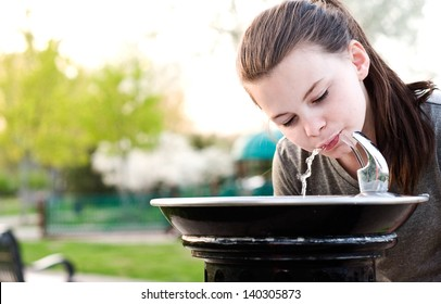An image of a young girl drinking from a water fountain